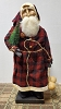 Medium Santa with Red and Black Coat Holding Bottlebrush Tree and Gourds